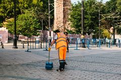 Istanbul, June 15, 2017: janitor in bright orange uniform sweeping the tile on the street in Sultanahmet district. Stock Image