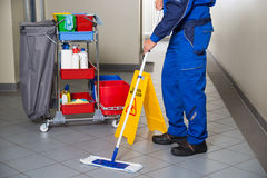 Janitor With Broom Cleaning Office Corridor Stock Photos