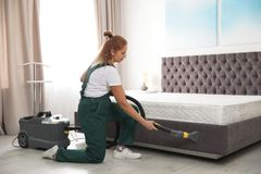 Janitor cleaning bed with professional equipment. In room royalty free stock photo