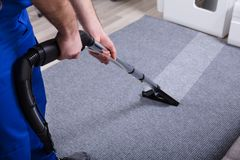 Janitor Cleaning Carpet. Janitor`s Hand Cleaning Carpet With Vacuum Cleaner royalty free stock photo