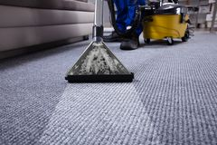 Janitor Cleaning Carpet. Janitor`s Hand Cleaning Carpet With Vacuum Cleaner stock image
