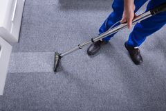 Janitor Cleaning Carpet. Janitor`s Hand Cleaning Carpet With Vacuum Cleaner royalty free stock photos