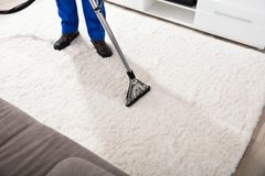 Janitor Cleaning Carpet With Vacuum Cleaner Royalty Free Stock Photography