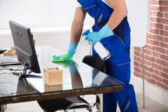 Janitor Cleaning Desk With Cloth In Office Royalty Free Stock Photo