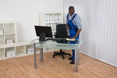 Janitor Cleaning Desk With Cloth. Young Male African Janitor Cleaning Desk With Cloth In Office Royalty Free Stock Photo