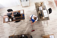 Janitor Cleaning Floor With Broom In Office. Elevated View Of Male Janitor Cleaning Floor With Broom At Workplace royalty free stock photography