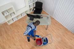 Janitor Cleaning Floor With Mop In Office. High Angle View Of Young African Janitor Cleaning Floor With Mop In Office Stock Photo
