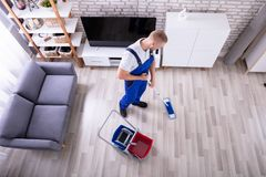 Janitor Cleaning Floor With Mop. Smiling Male Janitor Cleaning Floor With Mop In Living Room royalty free stock image
