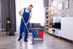 Janitor Cleaning Floor With Mop. Smiling Male Janitor Cleaning Floor With Mop In Living Room stock photos