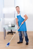 Janitor cleaning the floor in an office building Royalty Free Stock Image