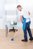 Janitor cleaning the floor in an office building. Handsome male janitor or cleaner cleaning the floor in an office building using a mop to wash the and disinfect stock photos