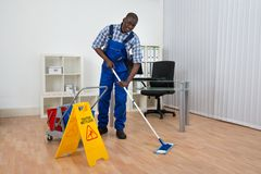 Janitor Cleaning Floor With Wet Floor Sign Royalty Free Stock Photo