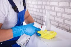 Janitor Cleaning Furniture With Cloth. Close-up Of A Young Male Janitor Cleaning Furniture With Yellow Cloth royalty free stock photography