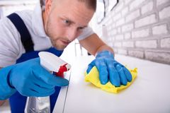 Janitor Cleaning Furniture With Cloth. Close-up Of A Young Male Janitor Cleaning Furniture With Yellow Cloth royalty free stock photos