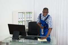 Janitor Cleaning Glass Desk With Cloth In Office. Young Male Happy African Janitor Cleaning Glass Desk With Cloth In Office Royalty Free Stock Photo