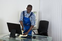 Janitor Cleaning Glass Desk With Cloth In Office. Young Male Happy African Janitor Cleaning Glass Desk With Cloth In Office Stock Photography