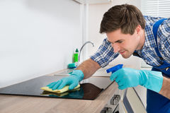 Janitor Cleaning Induction Stove. Young Happy Male Janitor Cleaning Induction Stove In Kitchen Stock Image