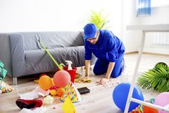 Janitor cleaning a mess. A janitor is cleaning a mess after a party Stock Photo