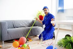 Janitor cleaning a mess. A janitor is cleaning a mess after a party Royalty Free Stock Images