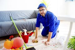 Janitor cleaning a mess. A janitor is cleaning a mess after a party royalty free stock photo