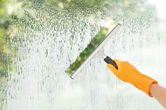 Janitor cleaning window with squeegee indoors. Closeup Stock Photography