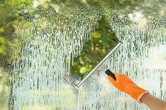 Janitor cleaning window with squeegee indoors. Closeup Stock Image