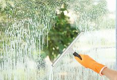 Janitor cleaning window with squeegee indoors,. Closeup Stock Photos
