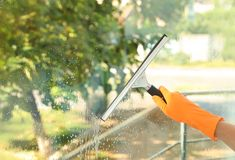 Janitor cleaning window with squeegee indoors. Closeup Stock Photos