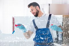 Janitor Cleaning Window With Squeegee. Young Male Janitor Cleaning Soap Sud On Window With Squeegee royalty free stock images