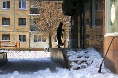 The janitor cleans snow from the annexe. The janitor cleans snow from the Annex to the building and snow-covered steps for unloading goods Royalty Free Stock Image