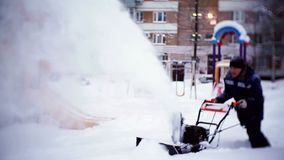 The janitor clears the track with a snowplow in the courtyard of an apartment building. Moscow stock video