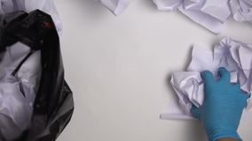 Janitor in gloves collecting paper in office, inefficient material usage, damage. Stock footage stock footage