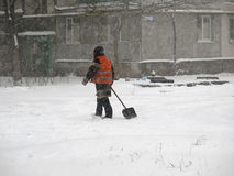 Janitor. Natural disasters winter, blizzard, heavy snow paralyzed the city, collapse. Snow covered the cyclone Europe Stock Image