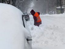 Janitor. Natural disasters winter, blizzard, heavy snow paralyzed the city, collapse. Snow covered the cyclone Europe Stock Images
