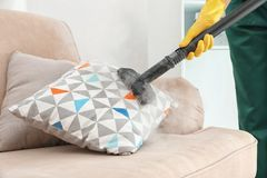 Janitor removing dirt from sofa cushion with steam cleaner. Closeup stock image