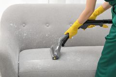 Janitor removing dirt from sofa. With upholstery cleaner, closeup royalty free stock images