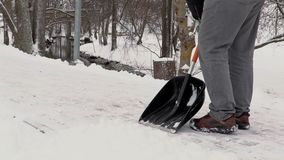 Janitor with snow shovel clean sidewalk from the snow stock video footage