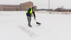 Janitor with snow shovel on path in snowy day stock video