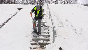 Janitor with snow shovel stepping down and cleaning stairs stock video footage