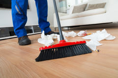 Janitor Sweeping Crumpled Papers On Floor Royalty Free Stock Image