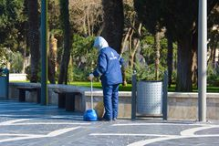 Janitor sweeping garbage in the park Stock Image