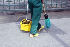 Janitor swept the city sidewalk from the fallen leaves. The janitor swept the city sidewalk from the fallen leaves Stock Image