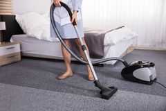 Janitor Using Vacuum Cleaner For Cleaning Carpet. Low Section View Of A Janitor Using Vacuum Cleaner For Cleaning Carpet In Hotel Room stock photos