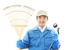 Janitorial cleaning service. The male worker who poses happily on white background Royalty Free Stock Photos