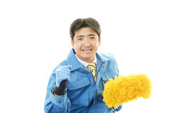 Janitorial cleaning service. The male worker who poses happily on white background Stock Photo