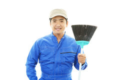 Janitorial cleaning service. The male worker who poses happily on white background Stock Photography