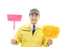 Janitorial cleaning service. The male worker who poses happily on white background Royalty Free Stock Photography