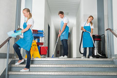 Janitors Cleaning Corridor With Cleaning Equipments Royalty Free Stock Photography