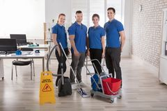 Janitors With Cleaning Equipments In The Office. Portrait Of Smiling Janitors With Cleaning Equipments And Caution Sign In The Office Stock Images