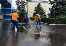 Janitors disperse brooms puddles after the rain in front of the airport of Simferopol Royalty Free Stock Images